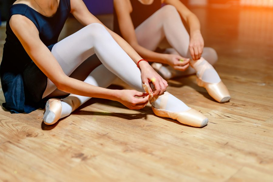 A close up of young ballet dancers tying shoes on studio floor.